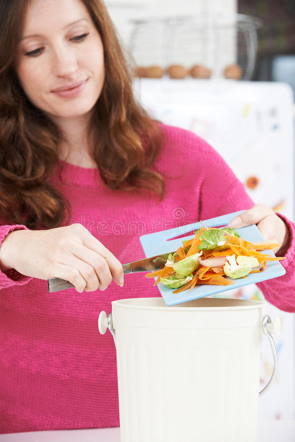 Woman Scraping Vegetable Peelings Into Recycling Bin royalty free stock photo