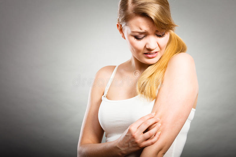 Woman scratching her itchy arm with allergy rash. Health problem, skin diseases. Young woman scratching her itchy arm with allergy rash royalty free stock photography