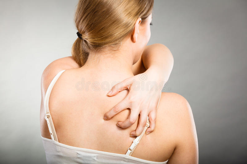 Woman scratching her itchy back with allergy rash. Health problem, skin diseases. Young woman scratching her itchy back with allergy rash stock images