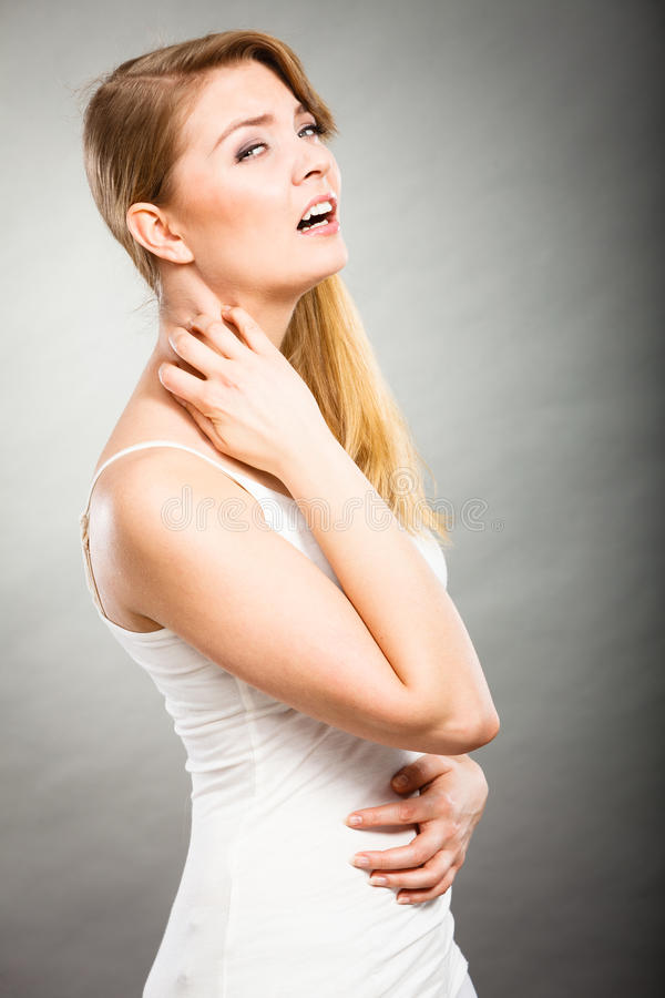 Woman scratching her itchy neck with allergy rash. Health problem, skin diseases. Young woman scratching her itchy neck with allergy rash royalty free stock image