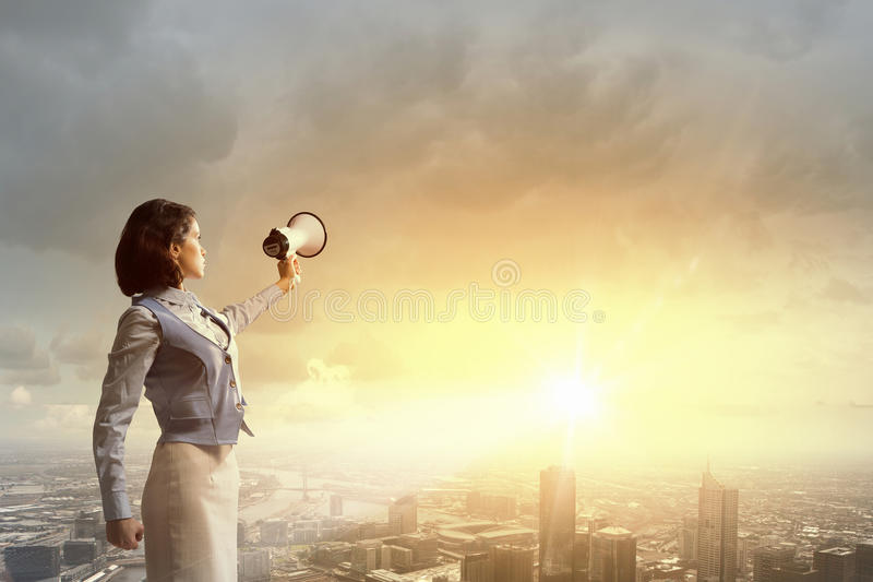 Woman scream in lodspeaker. Young businesswoman in suit proclaiming something in megaphone royalty free stock images