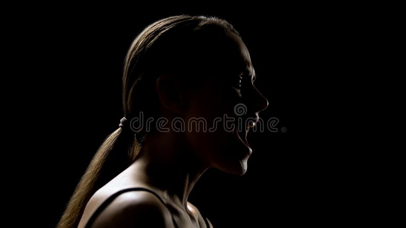 Woman screaming against black background, relieving stress, psychotherapy royalty free stock photo
