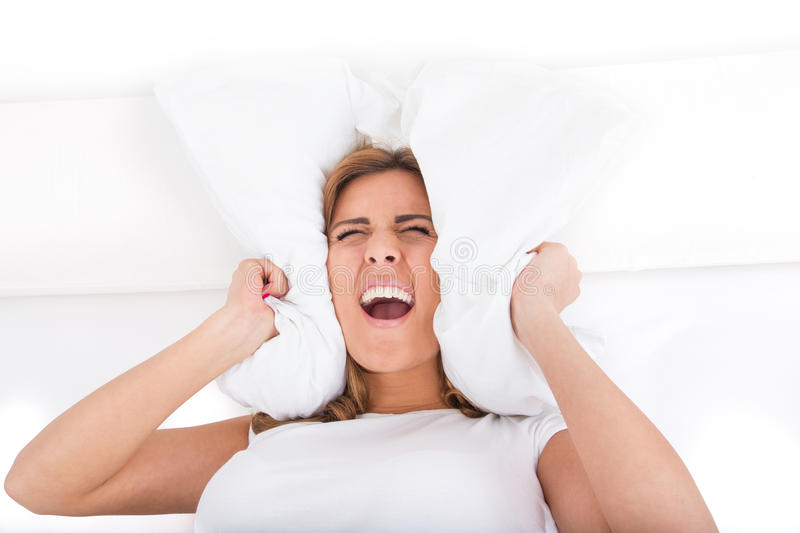 Woman screaming and covering her ears with pillow because of noise. Young beautiful screaming woman screaming and covering her ears with pillow because of noise stock images