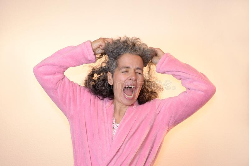 Woman screaming pulling on her graying hair bathrobe. A mature woman is screaming while pulling on her hair. Eyes shut, graying hair, pink bathrobe, plain royalty free stock images