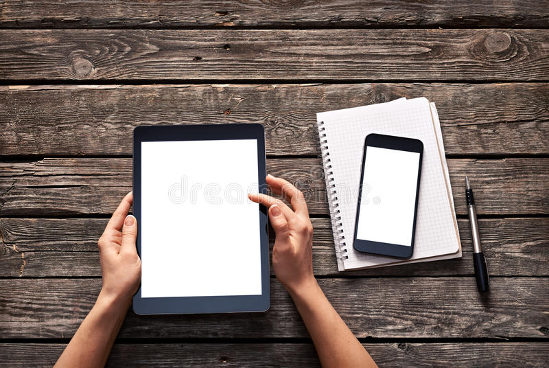 Woman scroll down screen of digital tablet. And smartphone is on notepad. Clipping paths included royalty free stock photos