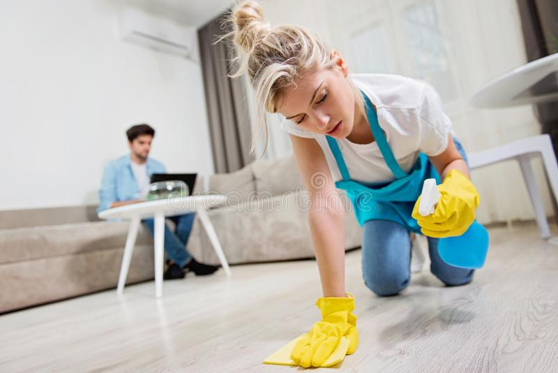 Woman scrubbing the floor while man is using a laptop royalty free stock image