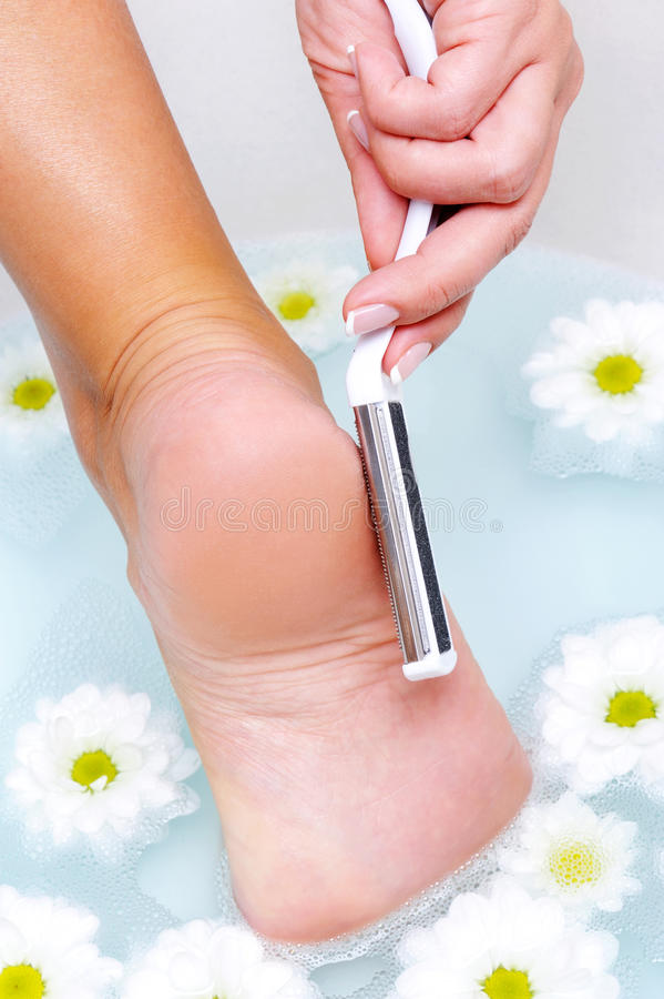 Woman scrubbing foot in water royalty free stock images