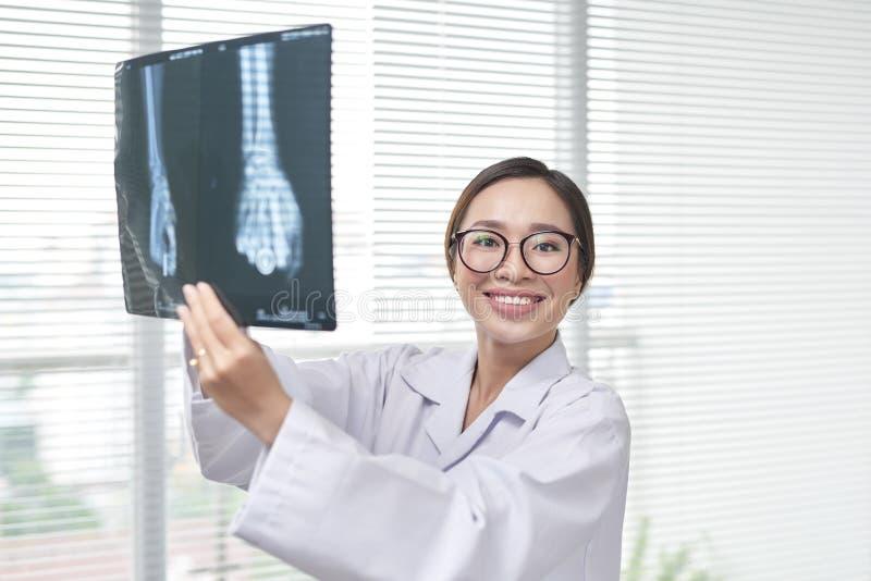 Woman in scrubs examining X-rays.  stock photos