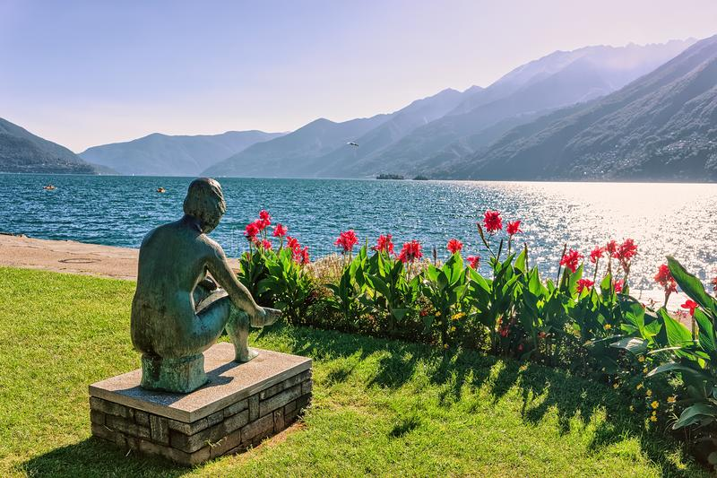 Woman sculpture at promenade in Ascona in Ticino in Switzerland. Sitting woman sculpture at the promenade at the luxurious resort in Ascona on Lake Maggiore in stock photo