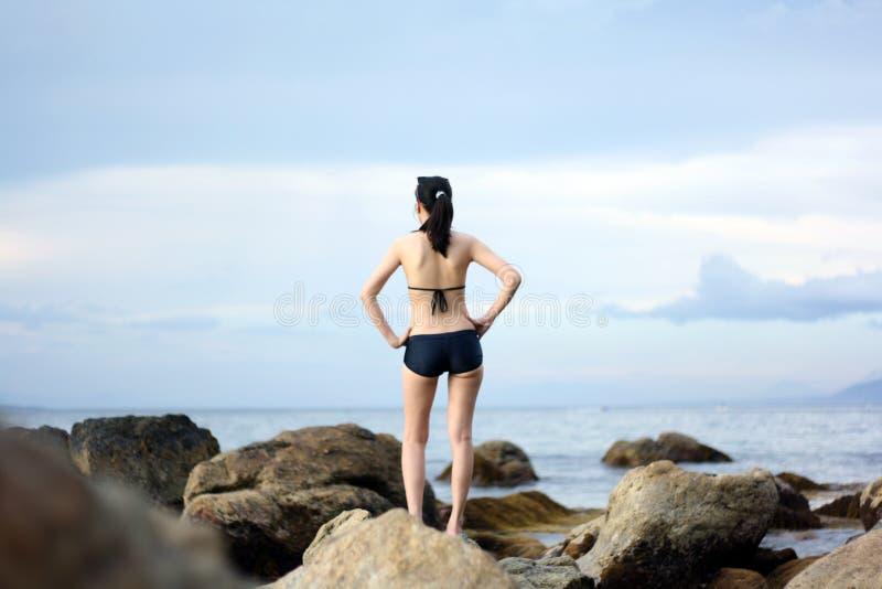 Woman on sea rock stock image
