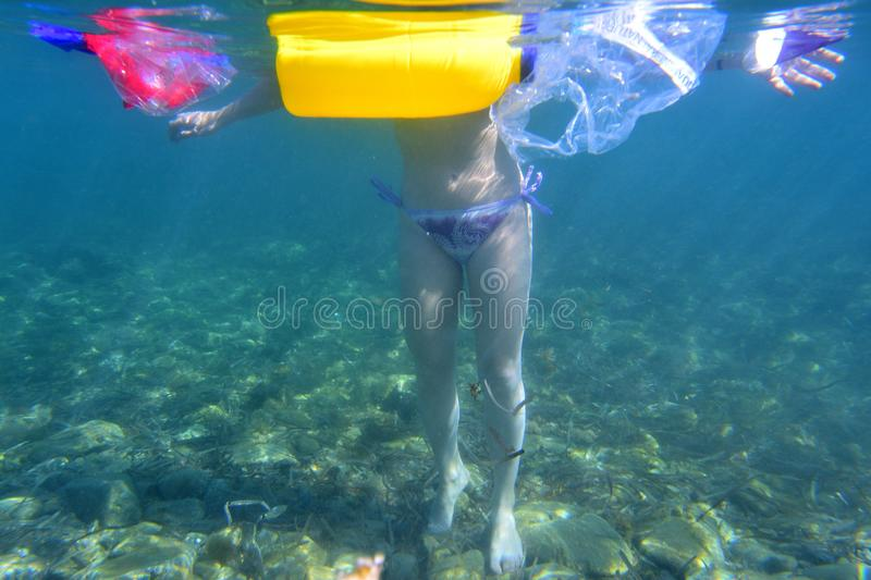 Woman in the sea surrounded by plastic garbage stock photo