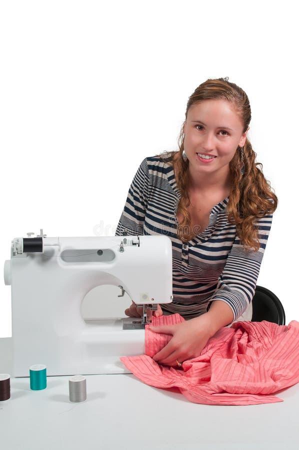 Woman Seamstress. Beautiful woman seamstress with a sewing machine royalty free stock photo