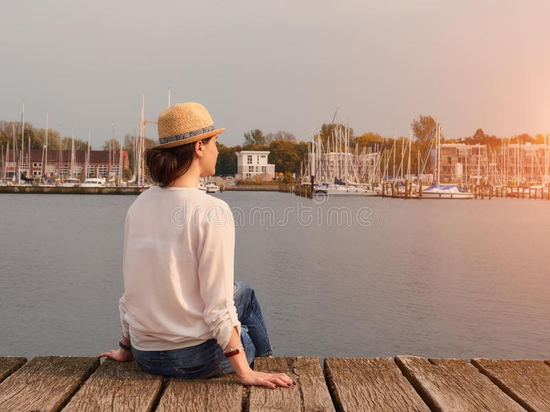Woman in seaport with yachts and sailboat on background. stock images