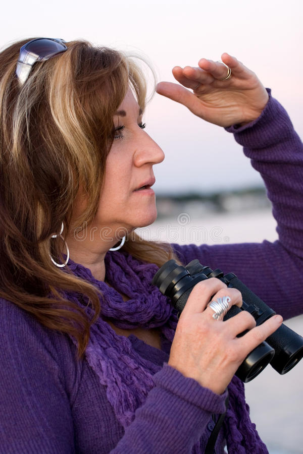 Woman Searching. A woman looks at something off in the distance with binoculars in her hands while at the seashore stock photo
