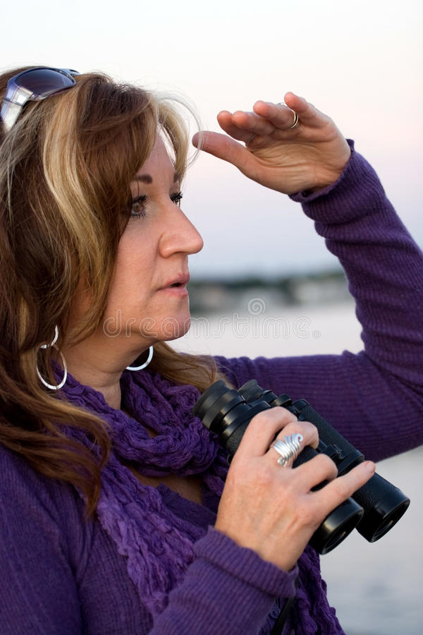 Woman Searching. A woman looking at something off in the distance with binoculars in her hands while at the seashore royalty free stock photos