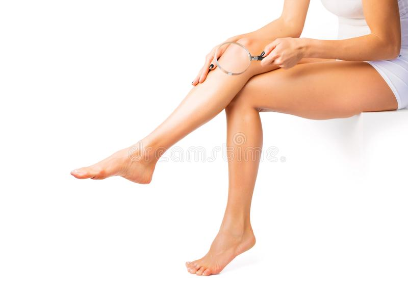 Woman searching for hairs on legs with magnifying glass stock photo