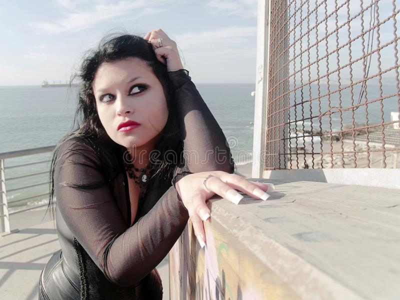 Woman at seaside. Gothic young woman posing outdoors at the seacoast of Valparaiso stock photo