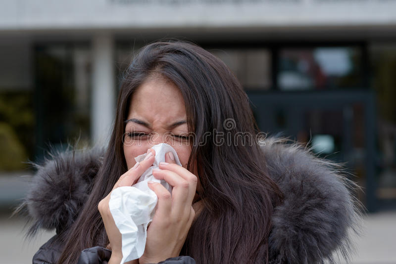 Woman with a seasonal winter cold and flu. Standing outdoors on an urban street in a furry jacket blowing her nose on a handkerchief royalty free stock photo