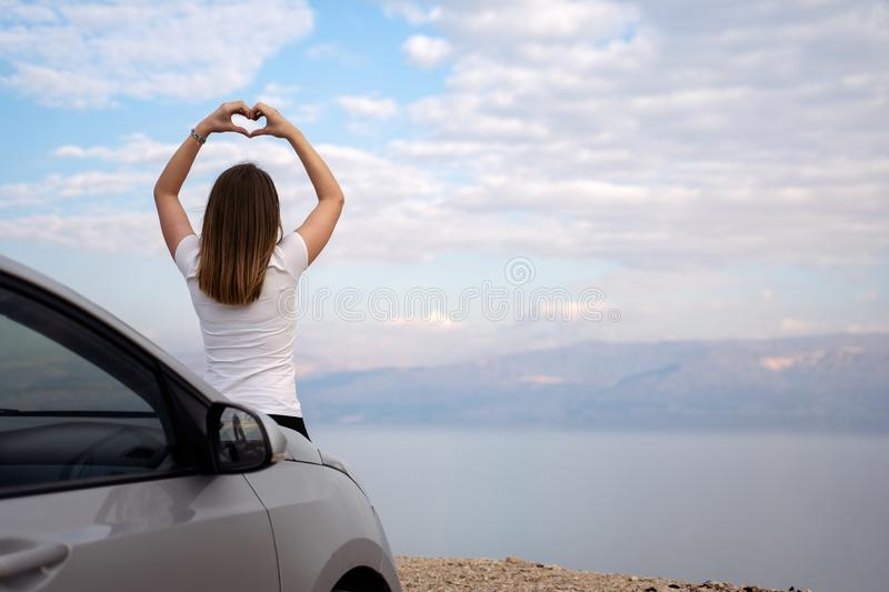 Woman seated on the engine hood of a rented car on a road trip in israel. Woman seated on the engine hood of a rented car. Dead sea as background. Hand Heart stock images