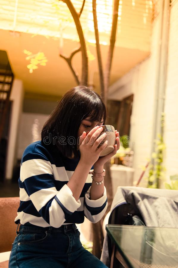 Woman Seated Outside Drinking from a Brown Bowl royalty free stock photography