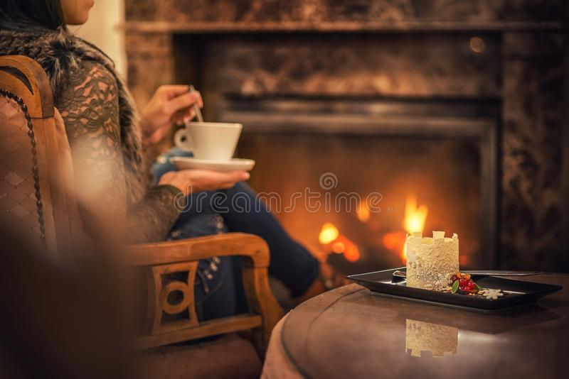 Woman seating near fireplace and drinking cup of coffee and eating beatiful winter dessert with chocolate, product photography for royalty free stock photo