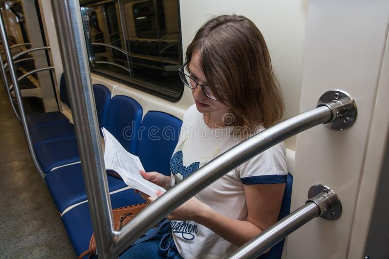 Girl seats in empty subway train. She is in blue jeans and white t-short royalty free stock photo