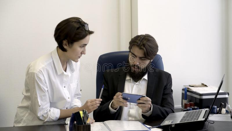 Woman secretary shows important documents to her bearded boss who is busy with playing smart phone games in the office royalty free stock image