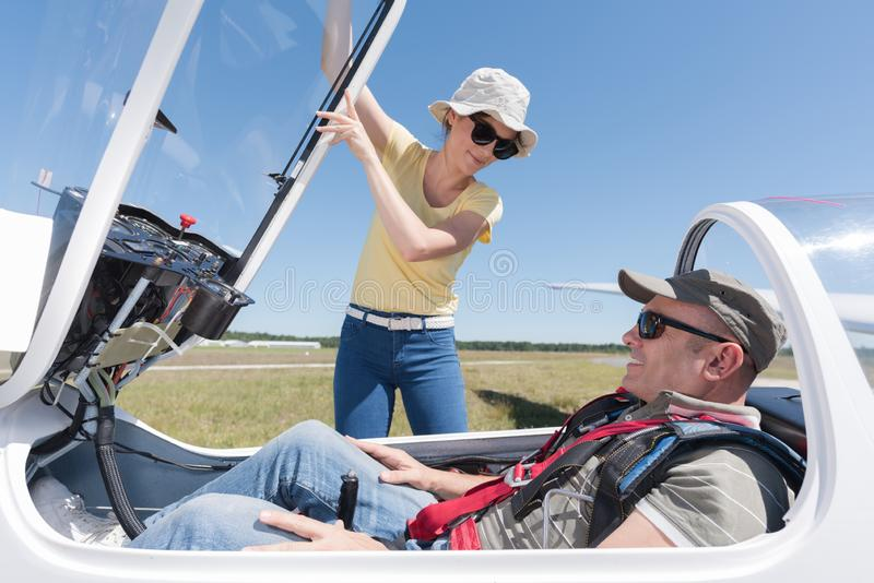 Woman securing cockpit over man in sailplane. Woman securing cockpit over men in sailplane man stock photography
