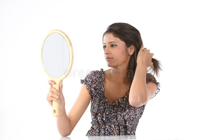 Woman seeing her hairstyle in makeup mirror stock photo