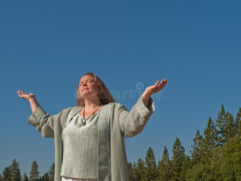 Woman seeking blessing. Mature woman standing in sun with arms raised while praying and seeking a blessing royalty free stock image