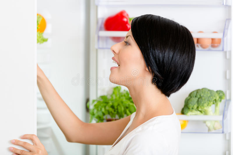 Woman seeks food in the opened fridge royalty free stock photo