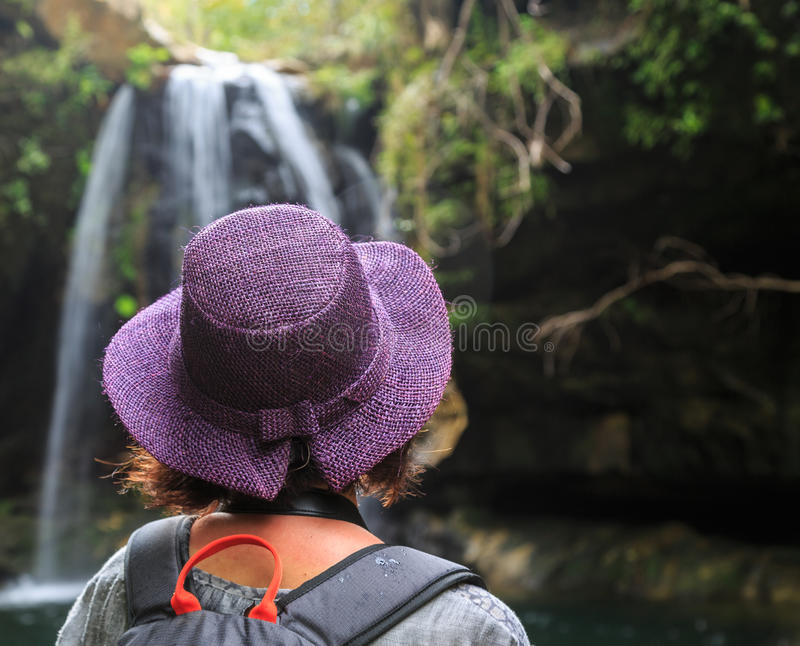 Woman seen from behind looking at a water fall. Woman with purple hat seen from behind looking at a water fall stock images