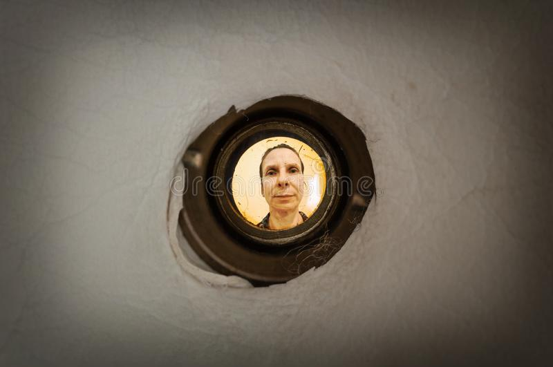 Woman seen through the peephole. Woman seen out of focus through the old dirty peephole of the front door of a dark apartment royalty free stock photos