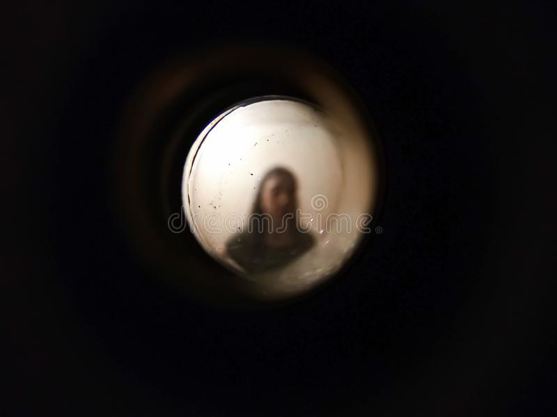 Woman seen through the peephole. Woman seen out of focus through the old dirty peephole of the front door of an apartment royalty free stock photography