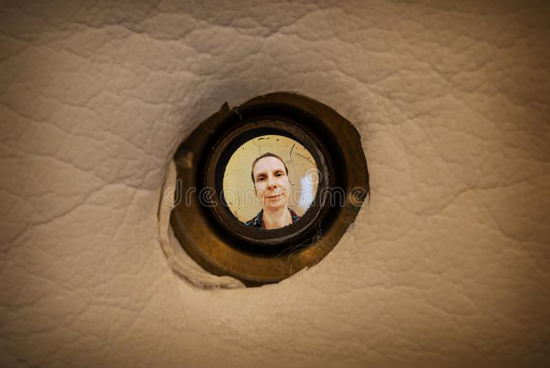 Woman seen through the peephole. Woman seen out of focus through the old dirty peephole of the front door of a dark apartment royalty free stock image