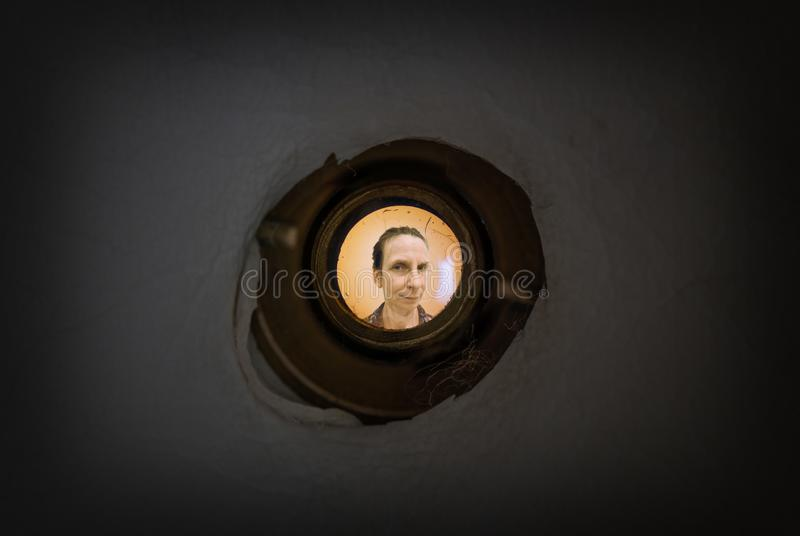 Woman seen through the peephole. Woman seen out of focus through the old dirty peephole of the front door of a dark apartment royalty free stock photo