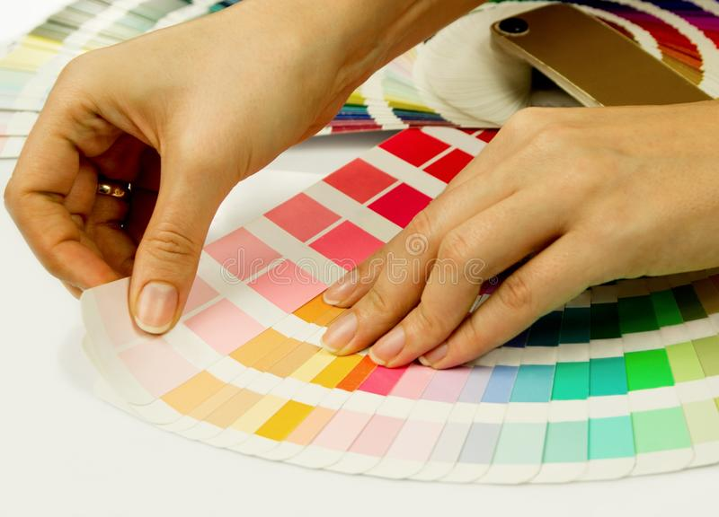Woman selecting color from Pantone swatches. Book stock photo