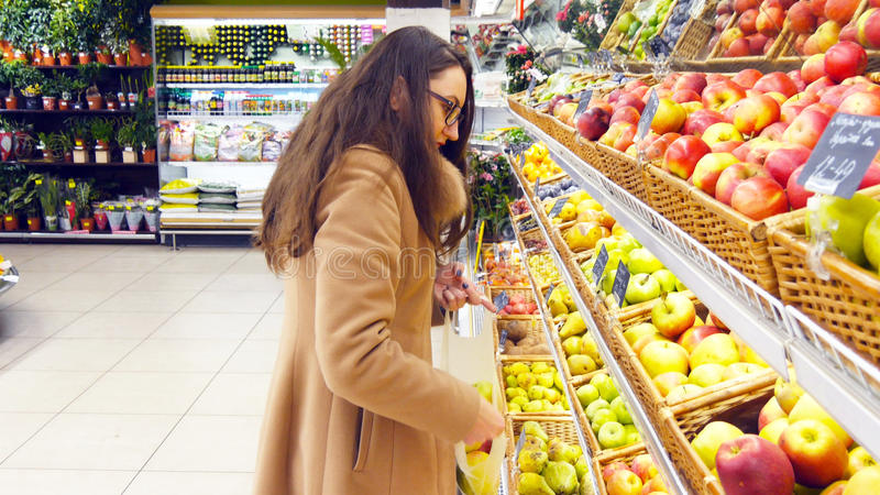 Woman selecting fresh red apples in grocery store produce department and putting it in plastic bag. Young pretty girl is stock photos