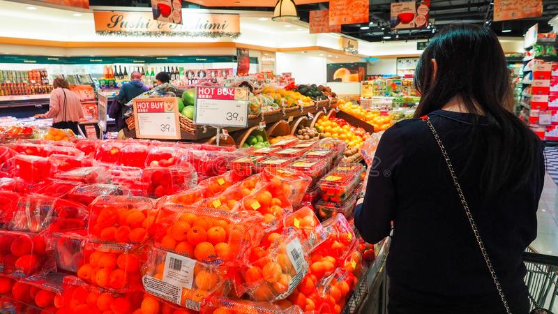Woman selecting .fruit fresh in grocery store produce department and putting it in plastic bag. Young pretty girl is choosing . stock images