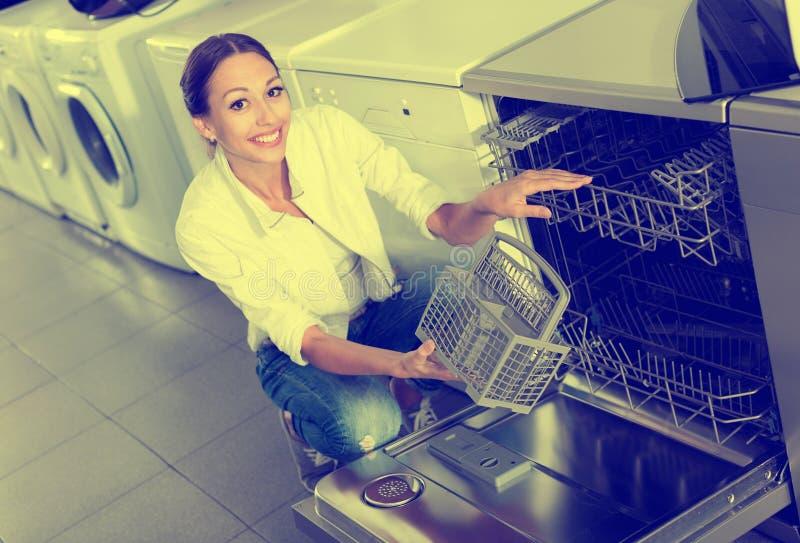 Woman selecting modern dishwasher royalty free stock photography