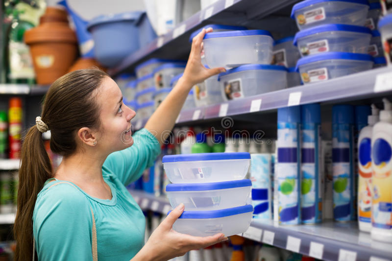 Woman selecting pails in store stock image