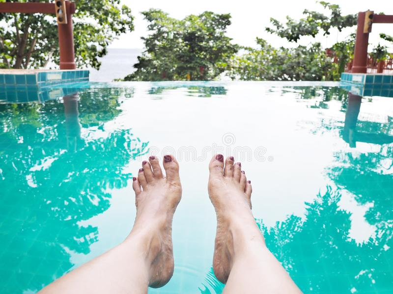 Woman selfie barefoot in the water at swimming pool stock photo
