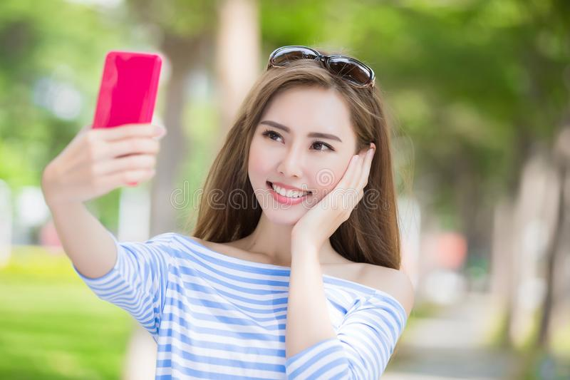 Woman selfie happily. Beauty woman selfie happily in the park stock image