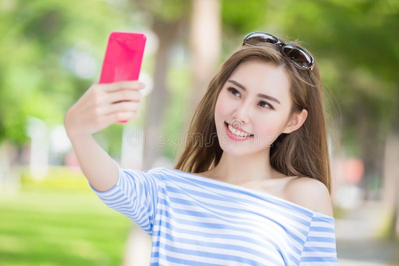 Woman selfie happily. Beauty woman selfie happily in the park stock photos