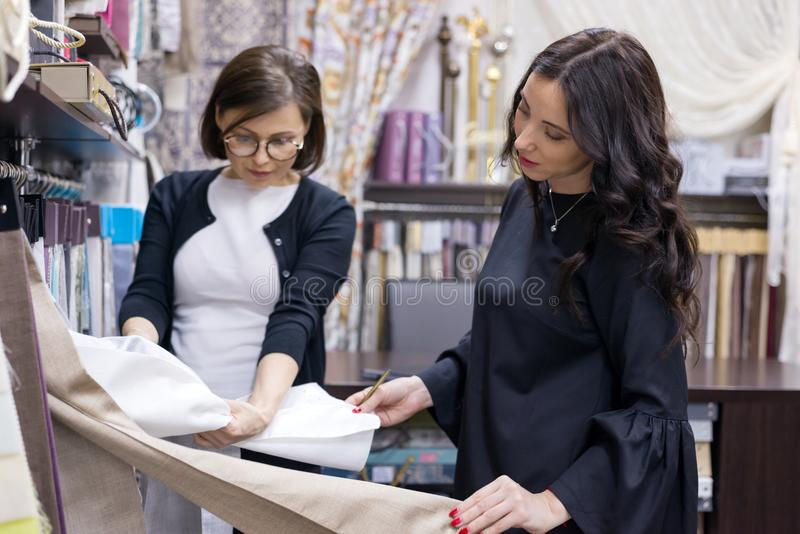Seller - textile designer advises woman buyer. Woman seller - textile designer advises women buyer. Selection of interior fabrics for curtains, bedspreads stock images