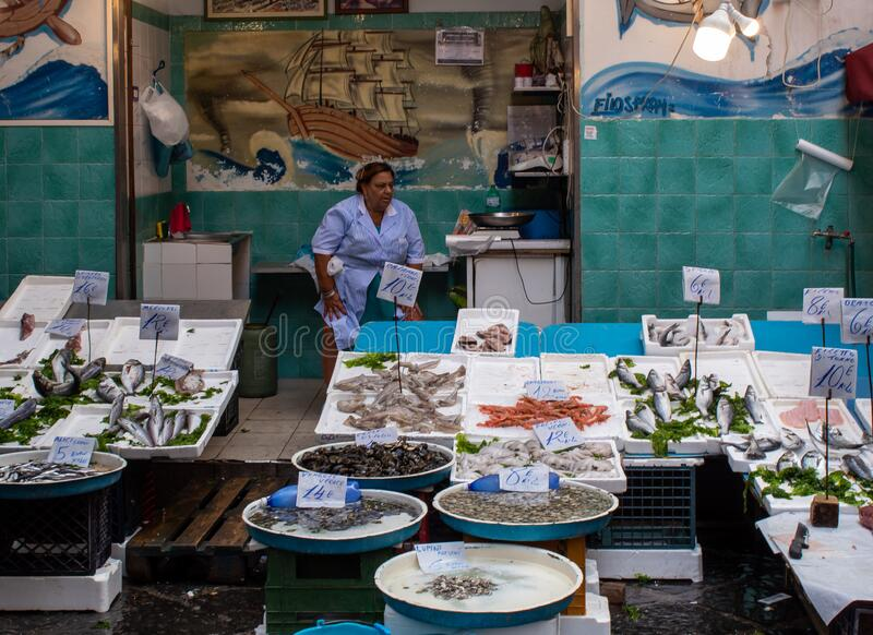 Woman selling fish at market in Naples royalty free stock images