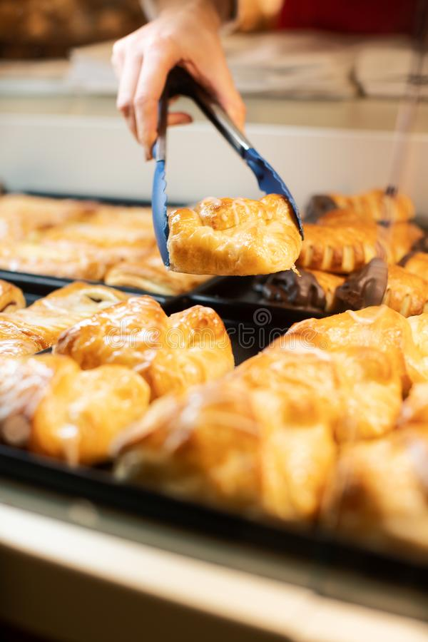Woman selling fresh pastries in bakery shop. Close-up on bread tongs royalty free stock photography