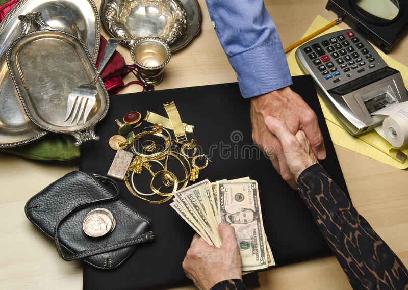 Woman selling gold and silver stock photography