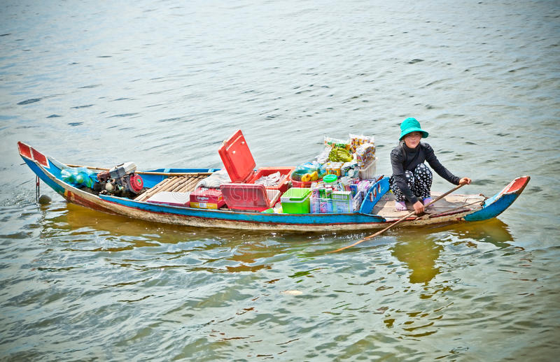 Woman selling goods in Ton le Sap village,Cambodia. TON LE SAP,CAMBODIA, NOV 22, 2013: Unidentified Cambodian woman rowing her sampan and selling goods in Ton royalty free stock photos