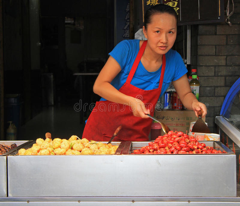 Woman is selling snacks outdoor in Wuhan, China. Wuhan, China - June 22, 2015:woman is selling snacks outdoor in Wuhan, China stock photo
